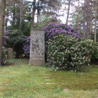 Gräbstätte neben weißem und lilanen Rhododendron